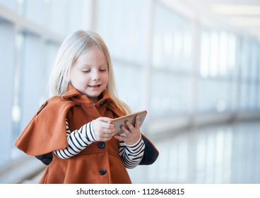 Concentrated little girl watching cartoon on mobile phone