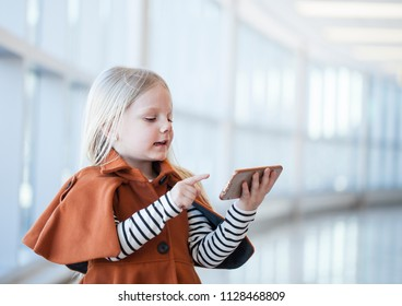 Concentrated little girl wearing orange coat playing smartphone