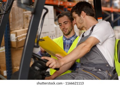 Concentrated loader and manager discussing goods and boxes they having to transport. Operator of forklift looking at yellow clipboard and holding hands on steering wheel.