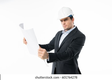 Concentrated male architect in hard hat examining blueprint  isolated on white