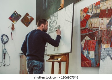 Concentrated male artist is drawing a dog on easel in his art studio, lots of pictures, creative atmosphere