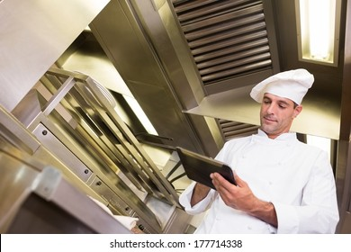 Concentrated male cook using digital tablet in the kitchen