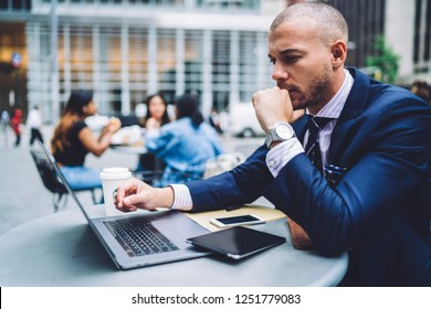 Concentrated male entrepreneur updating software on laptop connected to free public internet, thoughtful businessman reading and analyzing information from financial exchange web page on netbook
