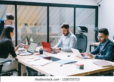 Concentrated male and female employees keyboarding on laptop devices in search information using wireless internet connection in modern office.Collaborative process of finance company