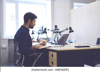Concentrated male journalist browsing information from social networks preparing article noting ideas, professional handsome copywriter working on creation advertising content for marketing website