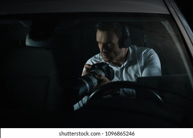concentrated male private detective in headphones spying by camera with lens from car