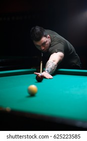 Concentrated man aiming the billiard ball.
