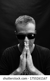 concentrated man with black background - sunglasses and hands together
