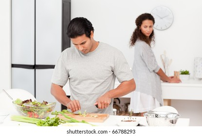 Concentrated man cutting vegetables with his girlfriend in the kitchen