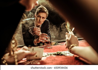 concentrated man with drink and poker cards looking at woman in casino