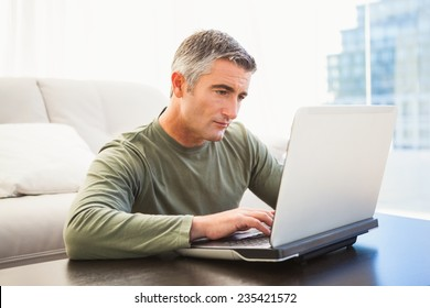 Concentrated man with grey hair using laptop at home in the living room