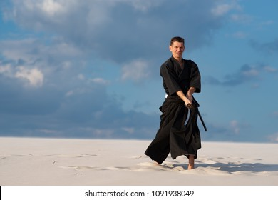 Concentrated man, in traditional Japanese clothes, with sword, katana, is training martial arts in desert during sunset - samurai on the blue cloudy sky background. Front view.