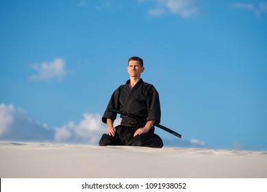 Concentrated man, in traditional Japanese clothes, with sword, katana meditating before the start of martial arts training in desert during sunset - samurai on the blue  sky background.
