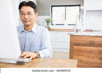 Concentrated man using computer at home