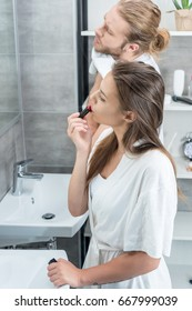 concentrated man wiping face while his wife applying red lipstick in bathroom in the morning