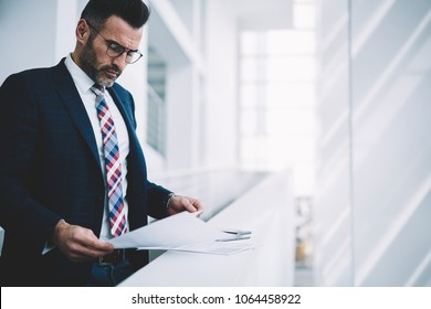 Concentrated mature businessman in formal wear analyzing financial reports standing in office of own company.Pensive male entrepreneur middle aged checking paper accounting documents