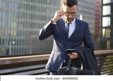 Concentrated mature businessman in trendy eyewear and elegant suit using application on smartphone for navigating in city being on working trip browsing right direction,serious male boss checking mail