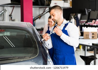 Concentrated mechanic performing car body repair at auto workshop with tools for repairing dents