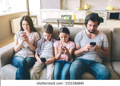 Concentrated members of family sit together on one sofa. Each of them has phone in hands. They look at them.