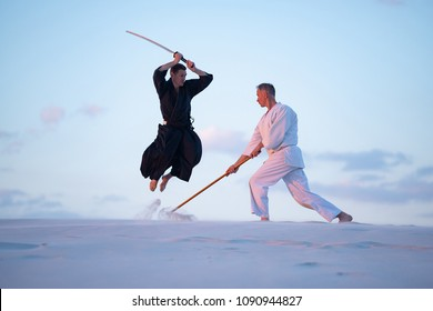 Concentrated men, in Japanese clothes, are practicing martial arts with a traditional Japanese weapon - a katana and jo, attack each other in the desert in the pink rays of the setting sun.