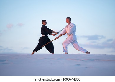 Concentrated men, in Japanese clothes, are practicing martial arts with a traditional Japanese weapon - a katana and jo,  in the desert in the pink rays of the setting sun.