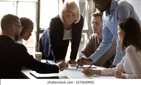 Concentrated middle aged female team leader leaning over table, looking at african american young employee pointing at financial document. Group of international specialists discussing project details