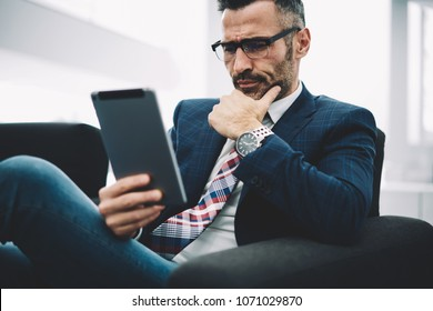Concentrated middle aged trader in formal wear reading attentively financial news on website on modern touch pad via free 4G internet connection.Pensive mature proud ceo watching video on tablet