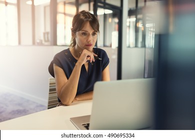 Concentrated middle aged woman working on her computer. Start-up office background