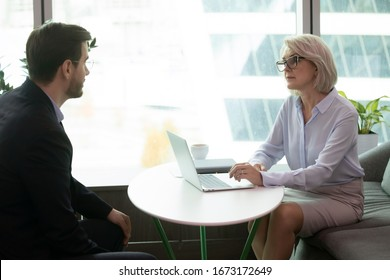Concentrated middle-aged businesswoman head meeting with male business partner in office, serious mature female CEO or boss listen to job applicant during work interview, employment, hiring concept