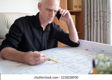 Concentrated middle-aged Caucasian man sitting at office table, examining blueprint of house and consulting with colleague on smartphone
