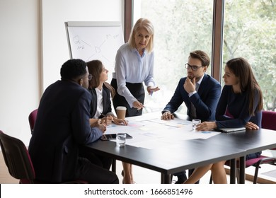 Concentrated middle-aged female leader head team meeting with multiracial colleagues in office, diverse businesspeople brainstorm discuss business project at briefing together, cooperation concept