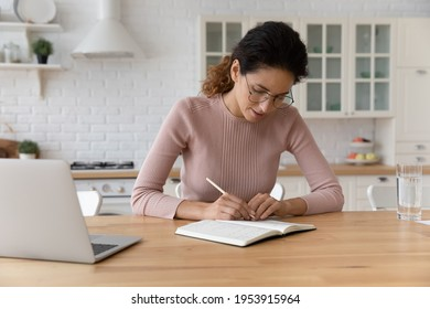 Concentrated millennial woman work with paper notebook plan day read check list of tasks take brief written notes. Focused latin businesswoman in glasses sit at home workplace write records to daybook
