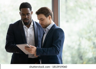 Concentrated multiracial businessmen discuss collaboration use modern tablet in office, focused successful diverse male colleagues brainstorm discuss business project on pad device at meeting.