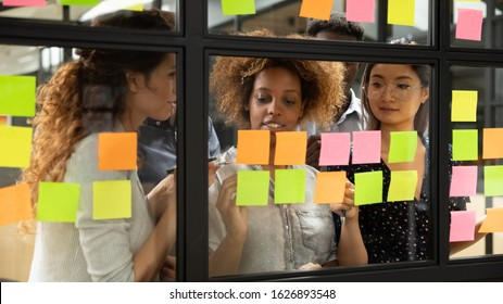 Concentrated multiracial diverse work group stand behind glass wall brainstorm develop startup strategy plan on post it pads, focused multiethnic colleagues write on sticky notes manage business ideas