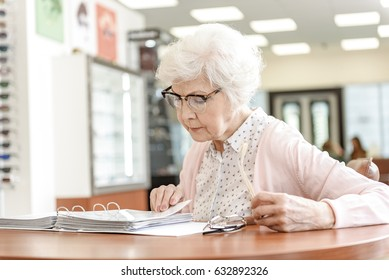 Concentrated old woman reading page