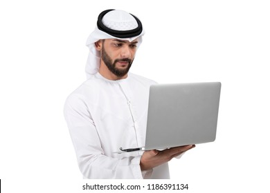 Concentrated on work. Confident young handsome Arab man in kandura working on laptop while standing against white background
