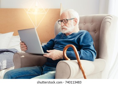 Concentrated pensioner looking at screen of computer