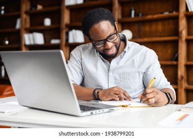 Concentrated positive hispanic man in eyeglasses thinking, taking notes while sitting at table with laptop and smartphone at home, author writing an idea for his book, study online, e-learning concept