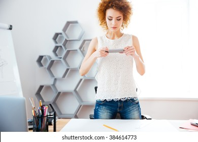 Concentrated pretty curly woman taking photos of her workplace using smartphone in office