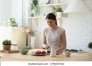 Concentrated pretty young woman preparing healthy breakfast at modern kitchen, active millennial girl vegan cutting fresh vegetable salad for lunch, positive female student cooking quick meal at home