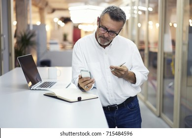 Concentrated proud CEO in eyewear and formal shirt texting feedback on smartphone sending files via 4G connection, pensive matured lawyer browsing information  reading news publication in office