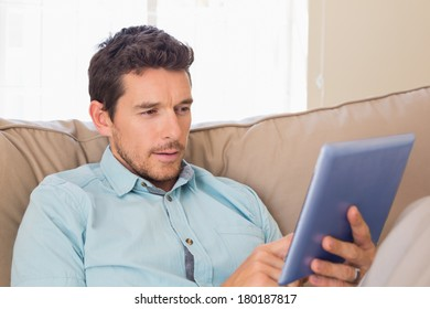 Concentrated relaxed young man using digital tablet on couch at home