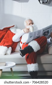 concentrated of santa claus with cup of coffee reading business newspaper