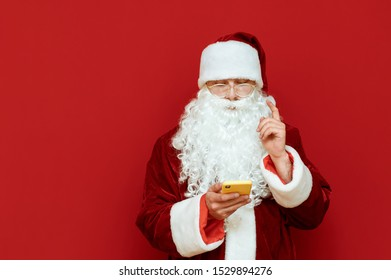Concentrated Santa Claus uses a smartphone and raises his finger, he has an idea, stands on a red background and looks at a smartphone screen. Santa Claus and technology. Christmas concept. Copyspace