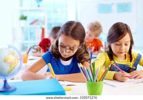 Konzentrierte Schulkinder, die mit einer Aufgabe beschäftigt werden