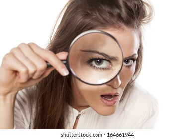 concentrated scowling young woman looking through a magnifying glass