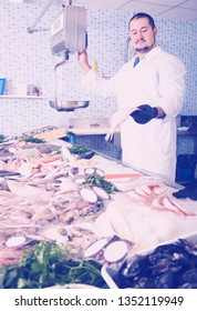 concentrated seller in white cover-slut standing near fish counter and weight fish