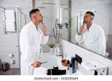 Concentrated serious man in a white bathrobe putting one hand on the bathroom sink while shaving beard with electric razor