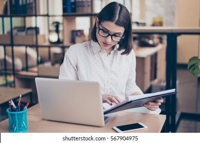 Concentrated smart young  businesswoman using her computer in office.