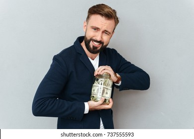 Concentrated smiling bearded man in business clothes trying opening jar with money over gray background